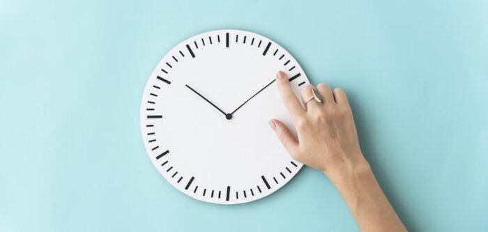mano che gira le lancette di un orologio: l'app rapportini di lavoro per gestire con consapevolezza il proprio tempo al lavoro
