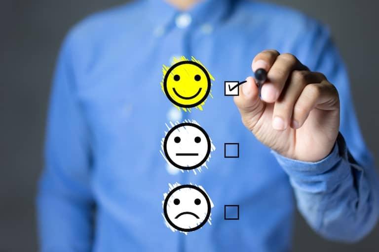 Employee experience: lavoratore che seleziona tra faccina felice e triste